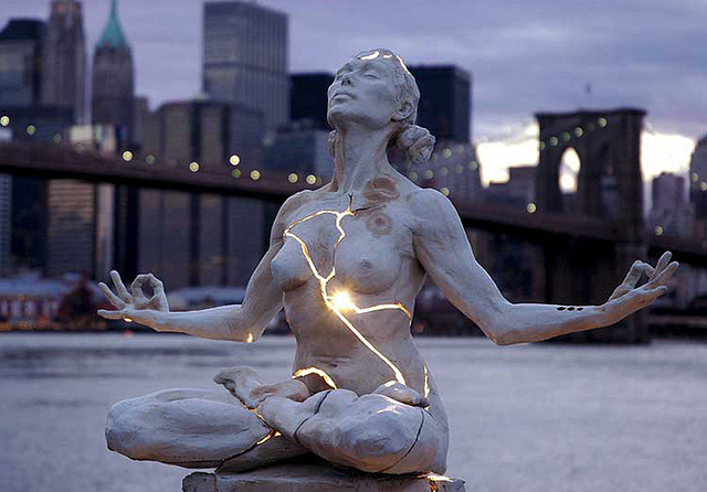 light-shining-out-of-cracked-meditating-woman-sculpture